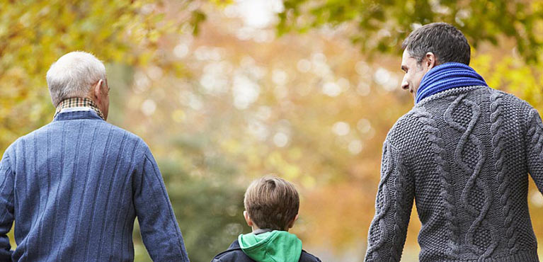 a multi generational family walks down a path in the fall